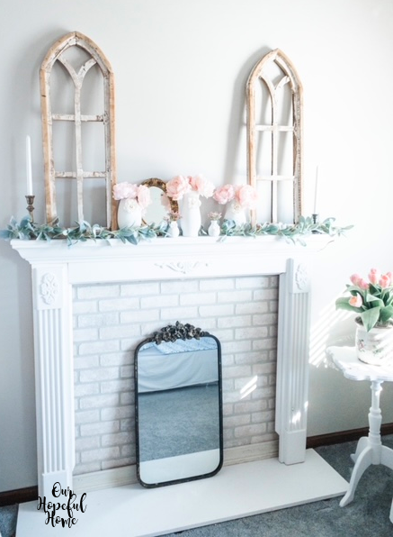 white faux fireplace mantel cathedral arches LED taper candles peonies