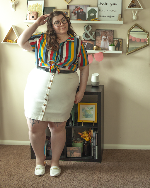 An outfit consisting of a multi colored rainbow inspired button down tie up crop top tied above a white button down midi skirt and white mules.