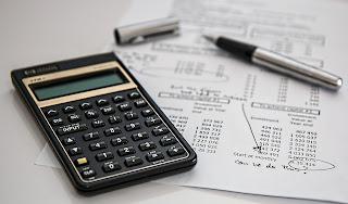 calculadora sobre a mesa, papel e caneta aberta.