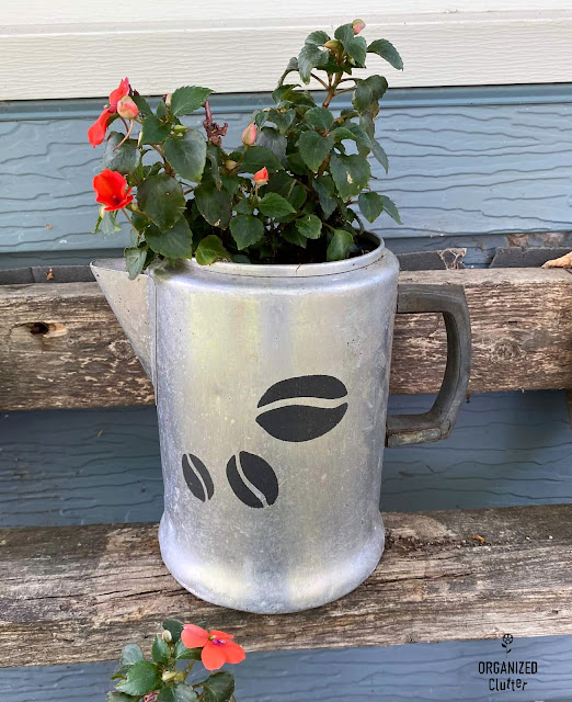 Photo of an aluminum coffeepot stenciled with coffee beans