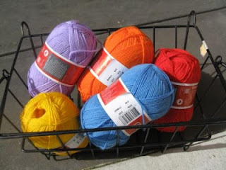 Five skeins of coloured acrylic yarn in a rectangular black wire basket. Colours are lilac, orange, red, light blue and golden yellow.