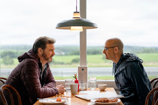 Firth and Tucci sitting across the table from each other in a diner with a daytime scene of lake and mountain outside the window