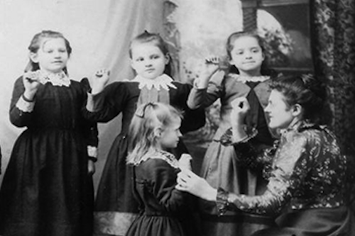Photo of ASL fingerspelling class, probably late 19th century