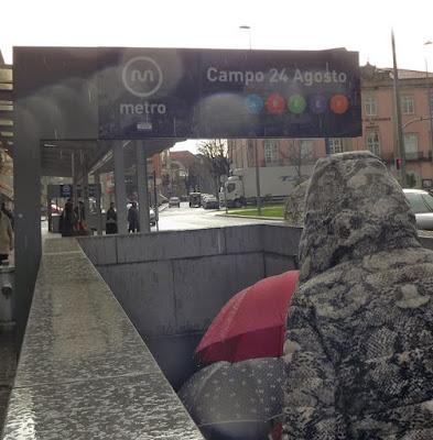 pessoas com guarda-chuva entrando na estação de metro no Porto