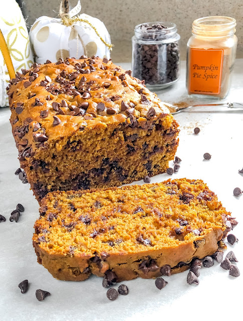 a sliced loaf of chocolate chip pumpkin spice bread surrounded with chocolate chips