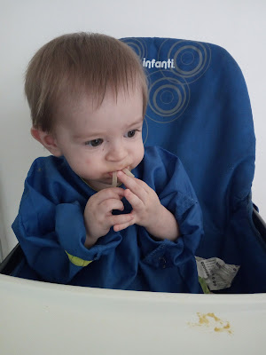 Baby Milestones At 11 Months Old - Image Shows Baby Eating Spaghetti In High Chair