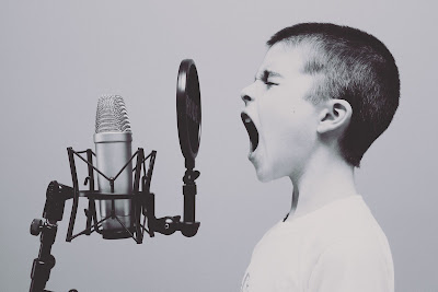 Black and white photo of a boy shouting or singing into a microphone. The microphone is a modern set up on a stand with a sound diffuser attached.