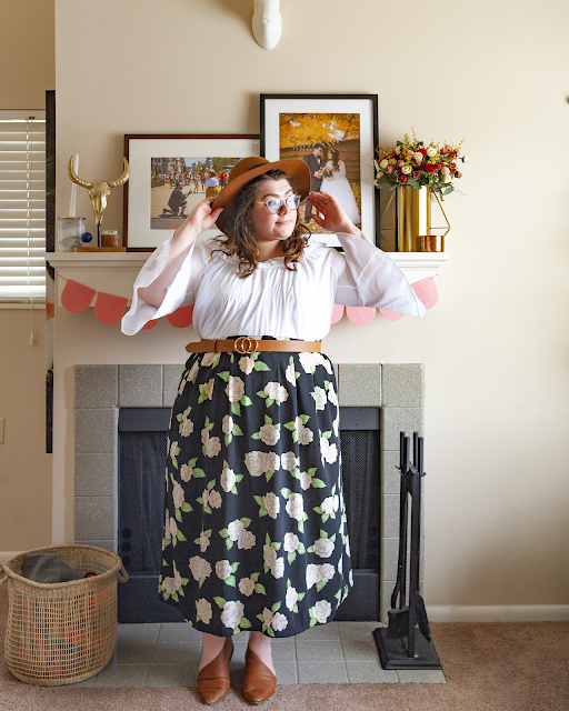 An outfit consisting of a brown panama hat, a white off the shoulder blouse tucked into a cream and green on black floral midi skirt and brown d'orsay flats.