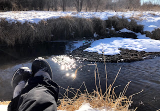 My crossed, booted feet on the bank of a creek bed covered in snow. Steam rising from the water in the sunny winter air.