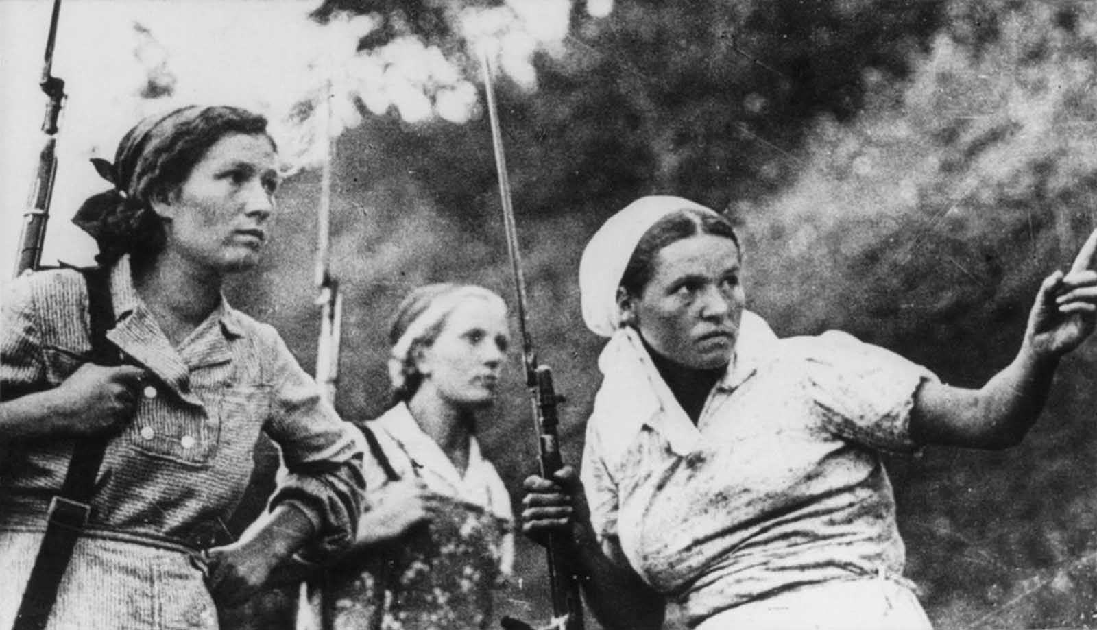 Three Soviet guerrillas in action in Russia during World War II.