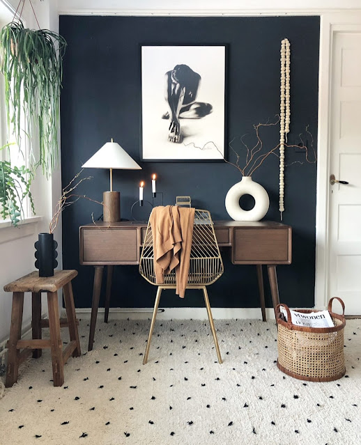 white modern donut vase on top of Bohemian desk with black painted focal wall