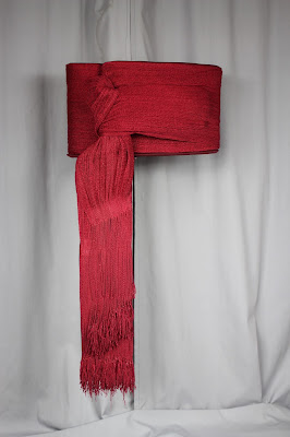 The after conservation treatment photograph of an 18th century red silk officer's sash, the sash was custom mounted and conserved, mount fabricated by Brigid Mountmakers, historic garments professionally and expertly conserved by textile conservator Gwen Spicer of Spicer Art Conservaton, Military artifacts, collectibles, antiques, display, restoration, repair, preservation