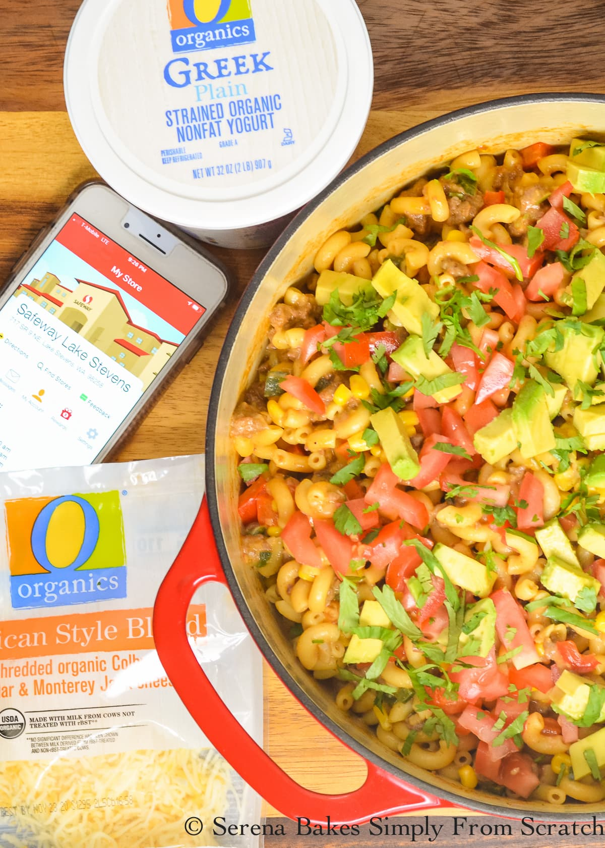 A large red pot filled with One Pot Taco Pasta with a O Organic Greek Yogurt on the top left of the photo and O Organic Mexican Shredded Cheese on the left bottom.