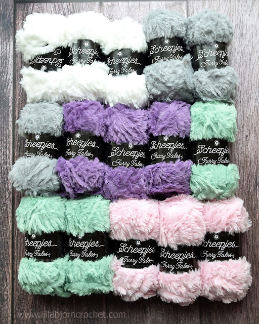 15 balls of fur yarn in different colors: pink, white, purple, grey and green