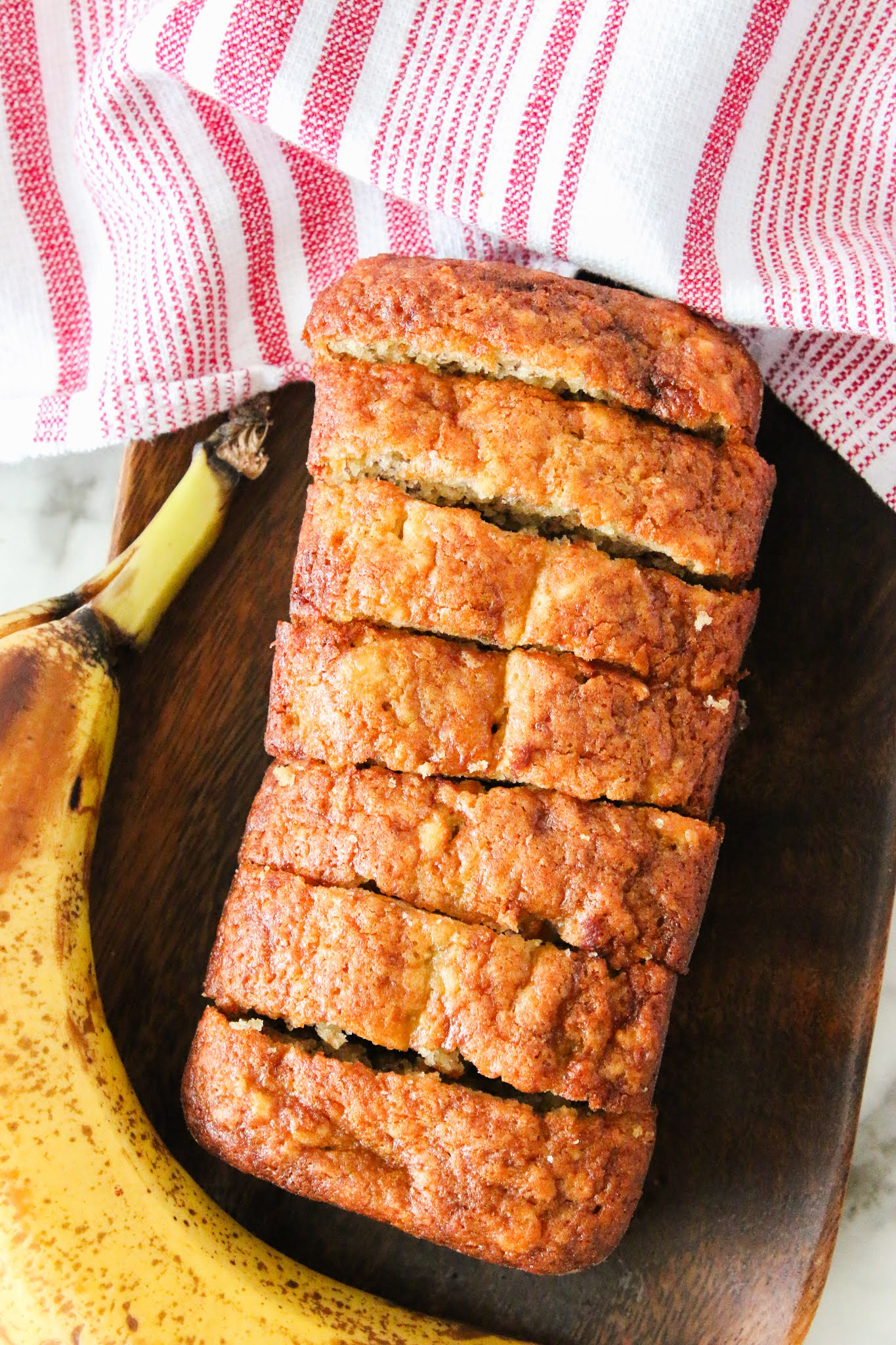 Mini loaf banana bread sliced on a wood platter with a red towel in the background