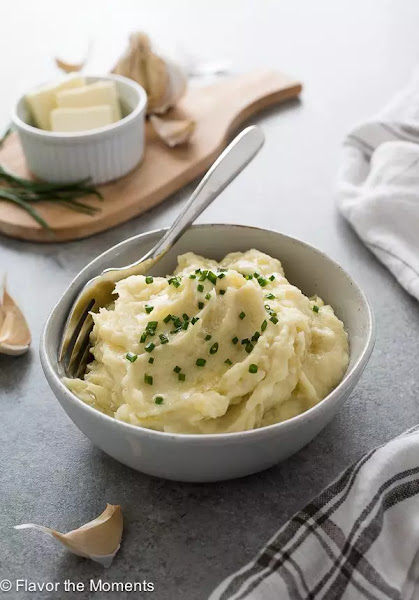 Side view of instant pot garlic mashed potatoes in a white bowl.