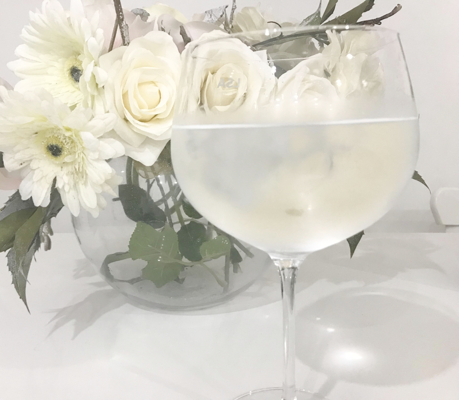 Glass of Water in a Wine Glass in front of a Vase of Flowers