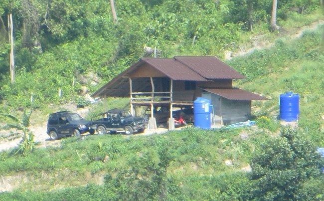 деревянный домик и два внедорожника