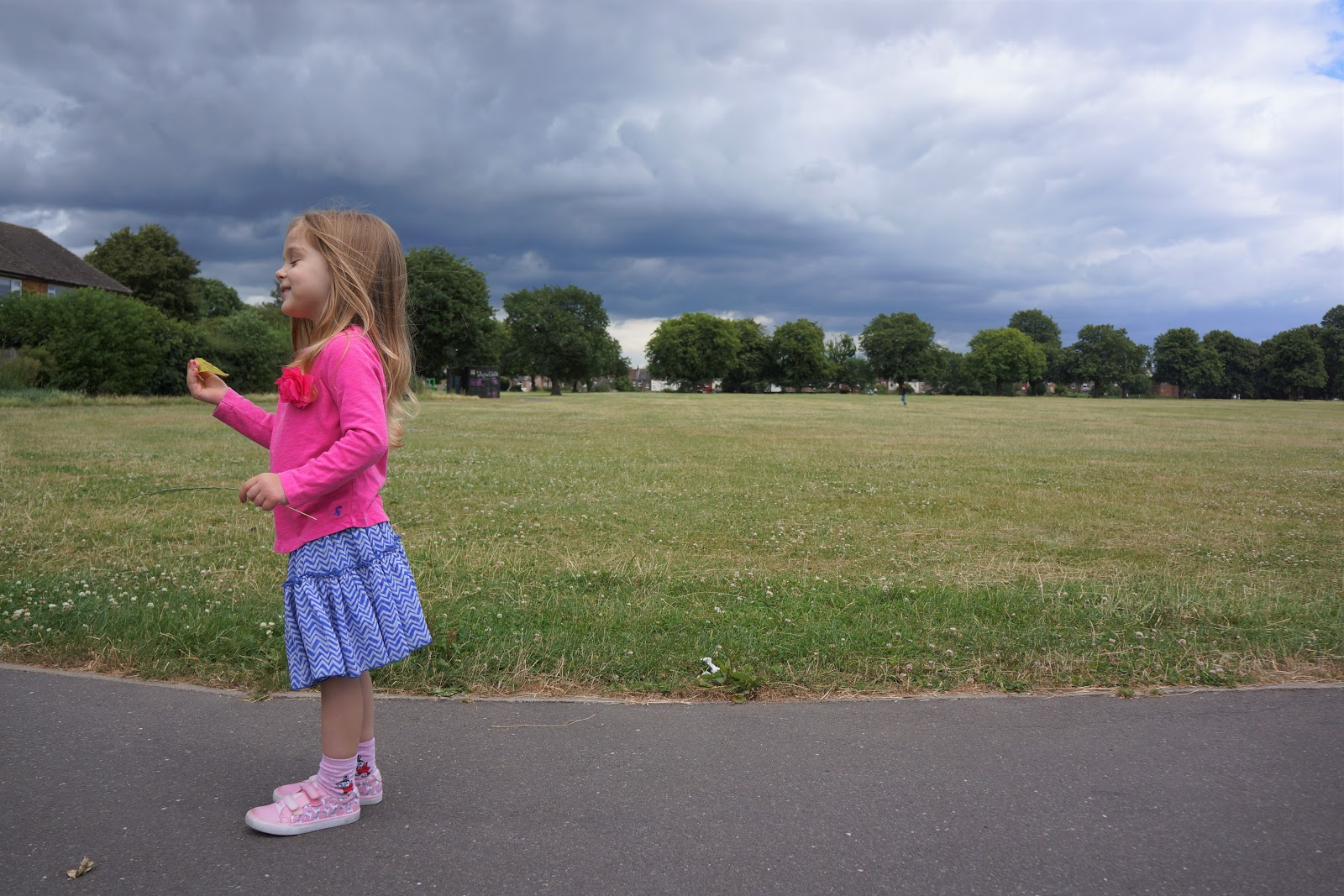 girl in a pink shirt and blue skirt standing in a park