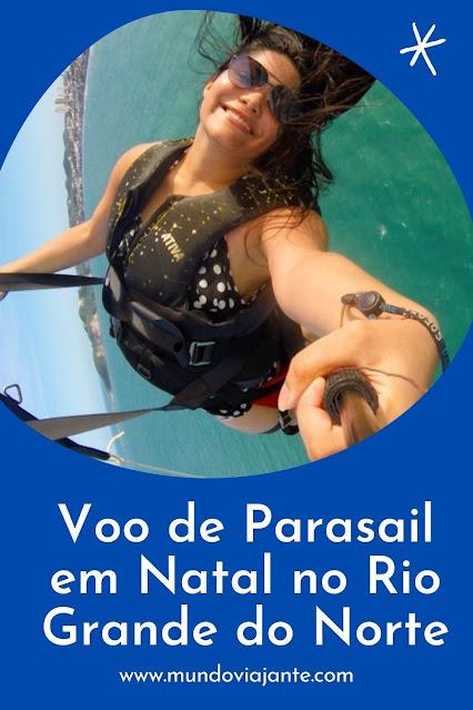 mulher voando de parasail coma agua do mar esverdeada ao fundo