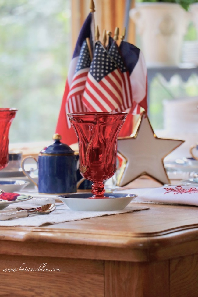 Labor Day patriotic French Country table setting with red glasses, white star, and blue sugar bowl.