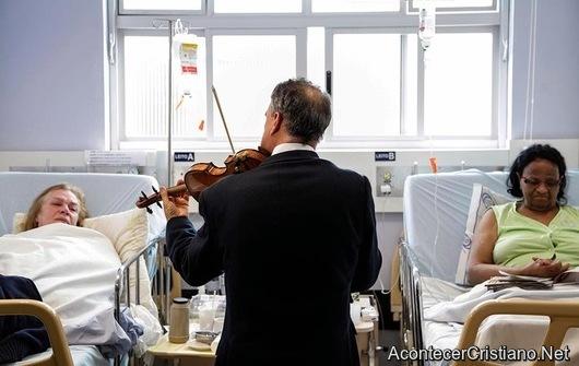 Musico toca himnos cristianos con violín ante enfermos de hospital