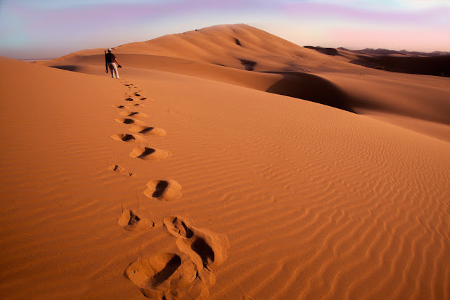 A man walking on the sand dunes of Maranjab Desert, Kashan