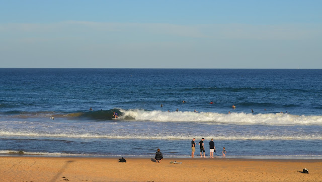 From top to bottom: pale blue sky, deeper blue ocean, white breakers with surfers behind them waiting for a break. To the left of the white breakers, a surfer has caught a wave. The thin line of white foam touches the shoreline where four adults and a child are waiting on the beach.