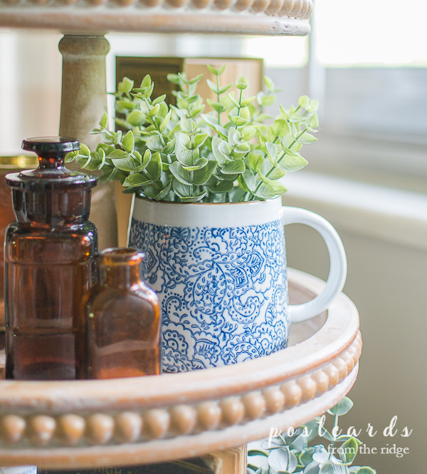 vintage amber bottles and blue and white mug on wood tiered tray