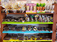 chocolate rabbits and chocolate baskets sit on wooden shelves packed with chocolate Easter treats and other Easter candies at Palmer's Candy in Sioux City, Iowa