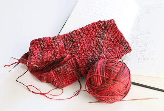 Red hand knit wool sock in progress on meatl double point knitting needles next to a ball of yarn and an open unlined book with project notes on a white background.