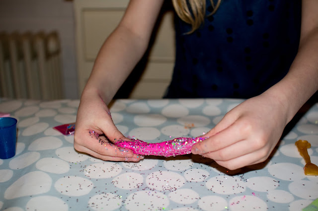 A table, hands and slime covered in large particle silver glitter