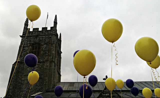 Purple and yellow balloons with church behind
