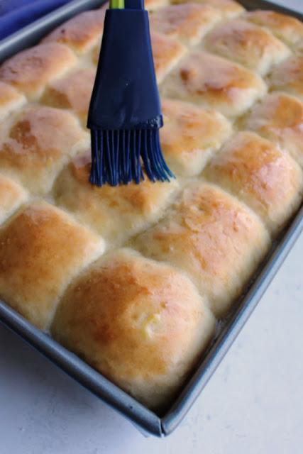 brushing melted butter over fresh baked golden pineapple rolls