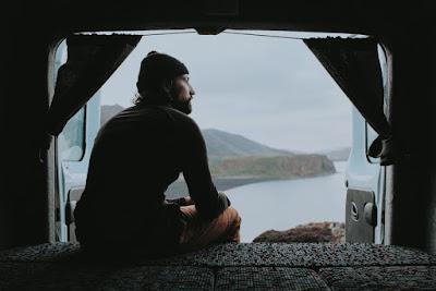 Viajero dentro de su campervan divisando el paisaje invernal