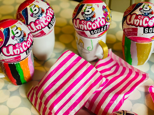 Miniature mugs painted at the party with Zuru 5 Surprise Unicorn Squad capsules on top and pink and white striped paper bags with sweets in