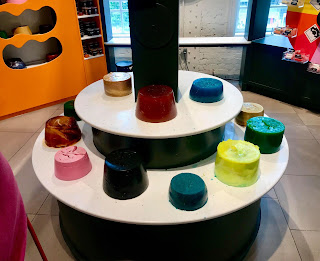 A. selection of small and large different coloured circular shower jellies on a circular white shelf on a bright background