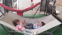 Децата си лежат на изложения хамак в мебелния магазин. Идея за стимулиране на кооперацията и послушанието на децата.