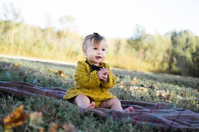 Baby Wearing Yellow Crochet Long Sleeve Dress Sitting on Brown Textile HD Copyright Free Image
