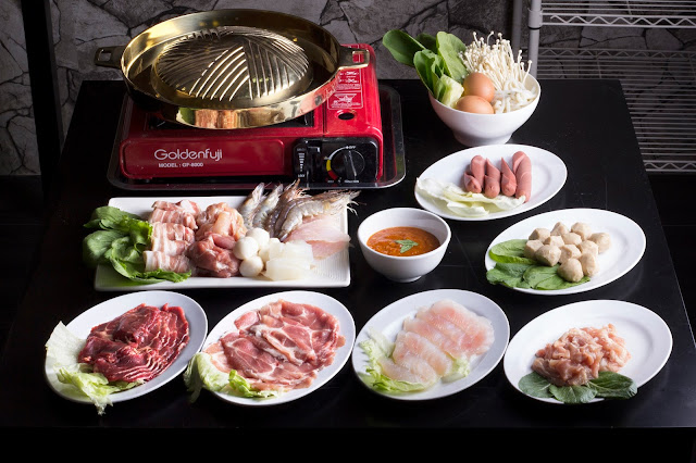 Photograph of Thai BBQ electric cooker, cut hotdogs, fishballs, sliced beef, sliced pork meat, sliced fish, prawns, curry sauce