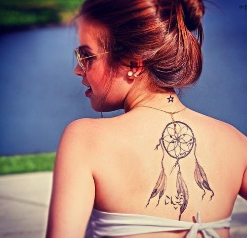 vemos a jovencita en la playa, tiene en su espalda el tatuaje de un atrapasueños