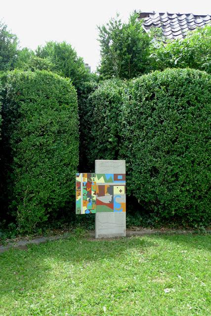 Stèle en béton plantée verticalement dans le sol et peinte avec des fromes colorées aux teintes crayeuses. Un volet en bois est accroché sur la gauche peint avec des formes plus petites