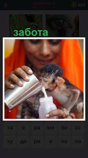 девушка из стакана кормит маленькую обезьяну молоком