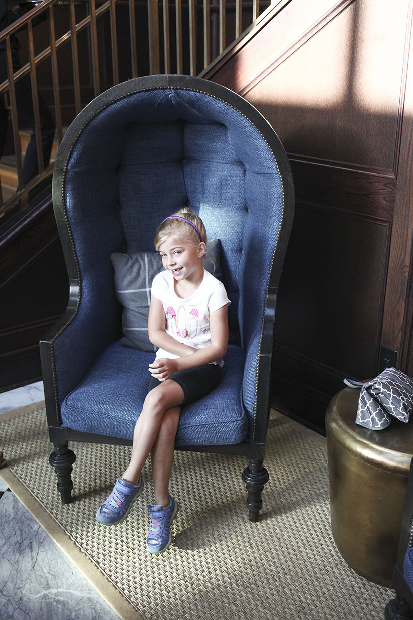Little girl smiles from cozy seat at Oxford Exchange in Tampa