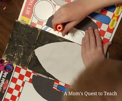 gluing the wings of the paper bag puppet penguin