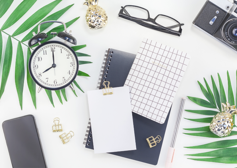 Desk with a clock and a notepad in a post about 7 ways you're wasting your time without even realising.