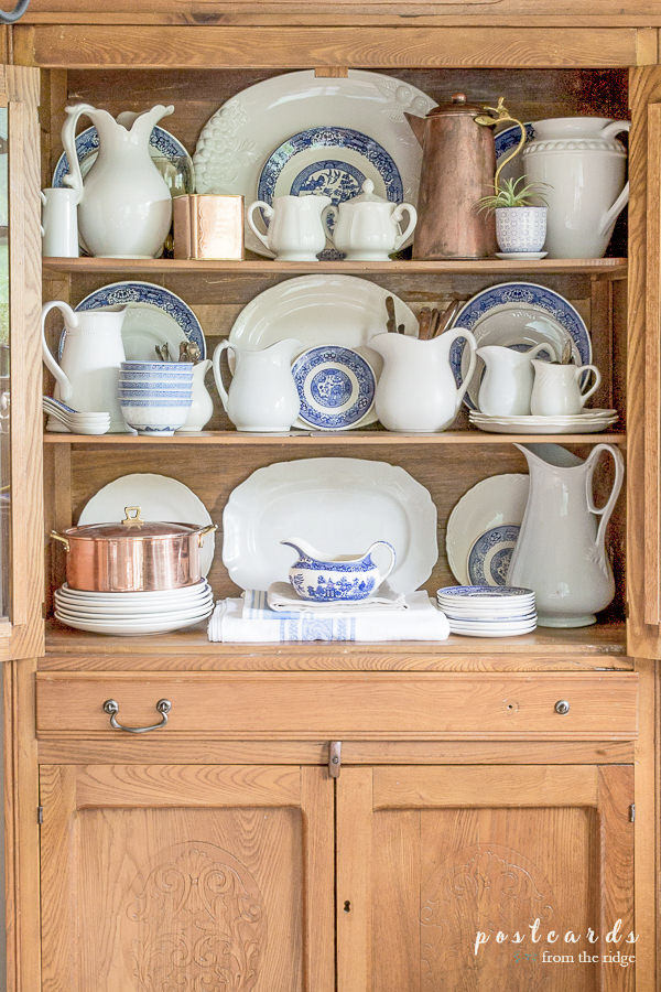 white ironstone, blue willow, and copper pieces in a vintage oak hutch