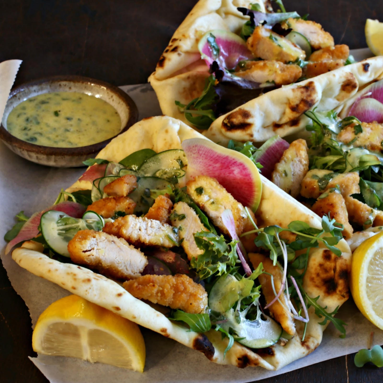 Recipe for crispy chicken pieces, mixed greens and a creamy lemon dressing served in naan bread or a tortilla.