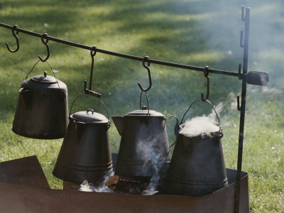 Four Metal Coffee Pots Steaming over an Outdoor Grill
