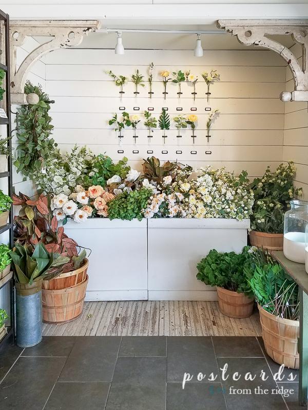 store display with lots of artificial flowers against white wall